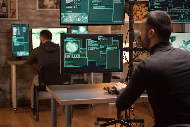 Vue arrière d'une équipe dangereuse de pirates informatiques travaillant sur un nouveau malware.
