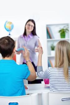 Vue arrière des étudiants avec les bras en salle de classe