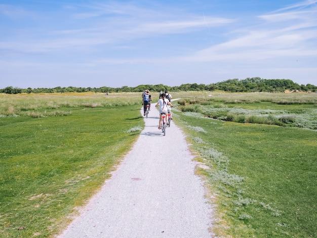 Vue arrière de la famille de cyclistes voyageant sur la route dans la région des dunes de l'île de schiermonnikoog.