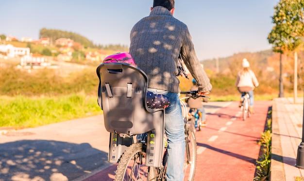 Vue arrière d'une famille heureuse avec des enfants faisant du vélo par la nature par une journée d'hiver ensoleillée