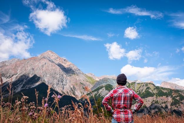 Vue arrière d'une femme active regardant et profitant de la vue sur la montagne et le ciel en vacances d'été - mode de vie des personnes et de l'environnement - nature du parc extérieur