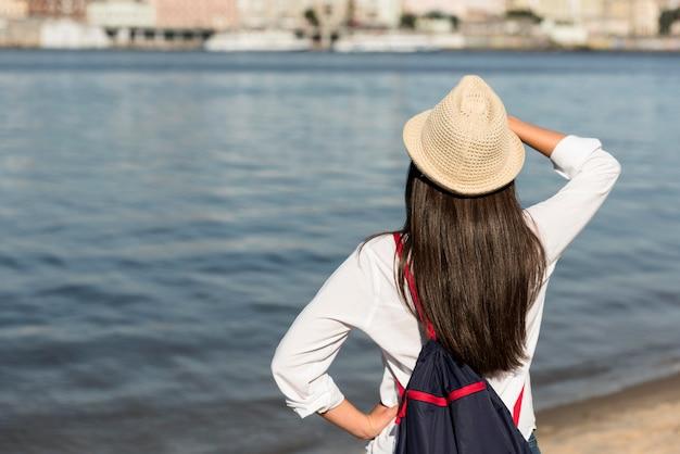 Vue arrière de la femme admirant la vue sur la plage