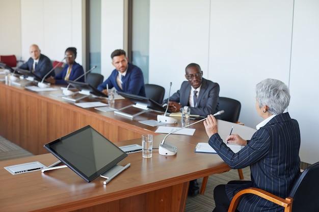 Vue arrière de la femme d'affaires mature parlant au microphone pendant que ses collègues assis à la table et l'écoutant à la salle du conseil