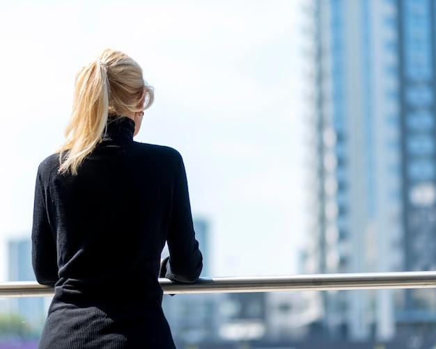 Vue arrière d'une femme d'affaires plus âgée en admirant la vue à l'extérieur