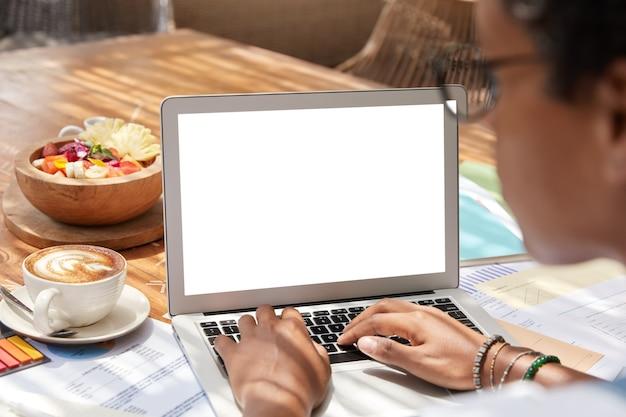 Vue arrière de la femme d'affaires travaille sur netbook