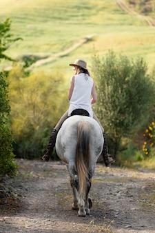 Vue arrière de la femme agricultrice équitation