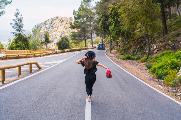 Vue arrière d'une femme anonyme aux pieds nus portant des chaussures rouges et touchant un chapeau élégant tout en marchant sur une route goudronnée le jour d'été à la campagne