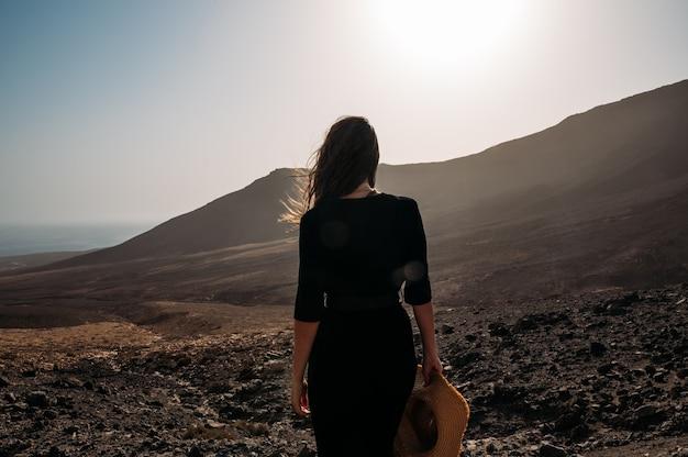 Vue arrière d'une femme anonyme en chapeau et robe debout au milieu de la vallée et profitant d'un coucher de soleil incroyable sur les collines avec un ciel nuageux coloré tout en voyageant à travers l'île de fuerteventura en espagne
