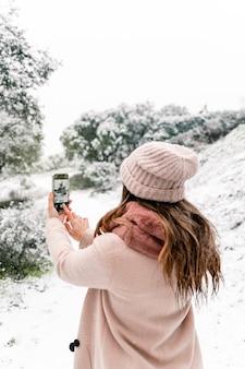 Vue arrière d'une femme anonyme dans des vêtements d'extérieur chauds debout dans les bois et prendre des photos de paysages enneigés tout en utilisant un smartphone