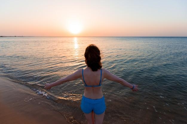 Vue arrière de la femme en appréciant le coucher du soleil