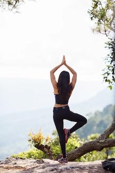 Vue arrière femme asiatique faisant du yoga à la montagne