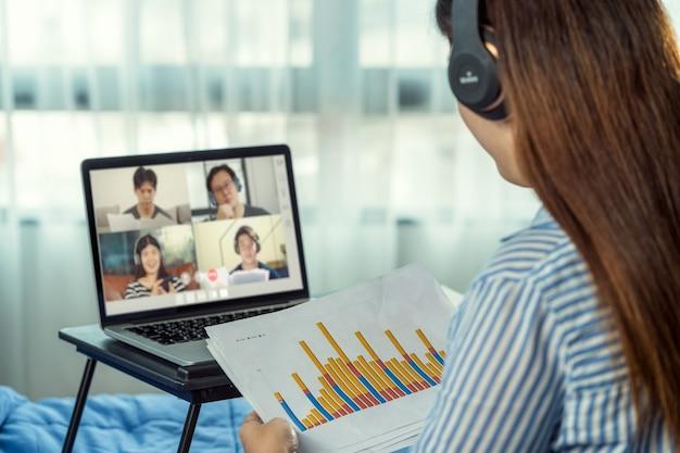 Vue arrière d'une femme asiatique travaillant et se réunissant en ligne par vidéoconférence avec un collègue