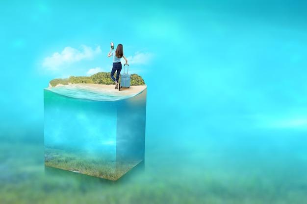 Vue arrière d'une femme asiatique avec une valise tenant un billet et un passeport sur la plage avec une vue sous-marine de l'eau bleue sur l'océan. notion d'environnement