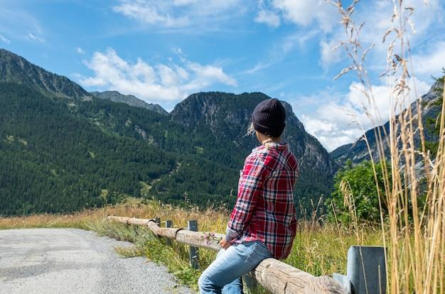 Vue arrière d'une femme assise et détendue regardant et profitant de la vue sur la montagne et le ciel en vacances d'été - mode de vie des gens et de l'environnement - nature du parc en plein air