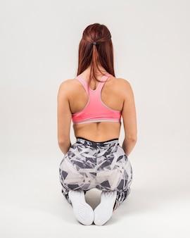 Vue arrière de la femme athlétique posant dans l'athleisure