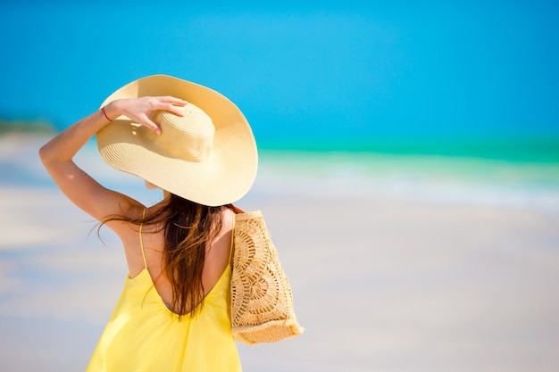 Vue arrière de la femme au grand chapeau pendant les vacances à la plage tropicale