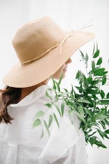 Vue arrière d'une femme aux cheveux bruns dans un chapeau tissé