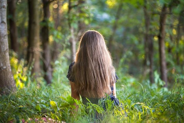 Vue arrière d'une femme aux cheveux longs, assis à l'extérieur dans la forêt, profitant de la nature.