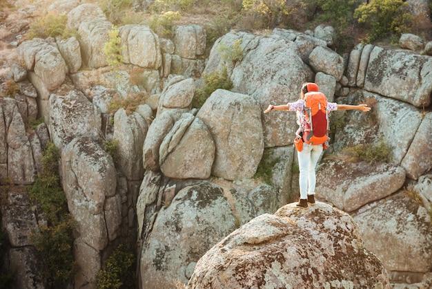 Vue arrière de la femme aventureuse près du canyon sur le rocher