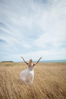 Vue arrière de la femme blonde debout dans le champ