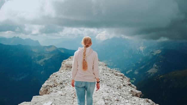 Vue arrière d'une femme blonde marchant au sommet de la montagne sous les nuages