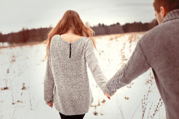 Vue arrière de la femme blonde marchant avec son petit ami sur la neige