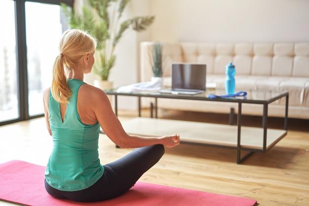 Vue arrière d'une femme blonde mature sportive assise en position du lotus sur le sol et faisant