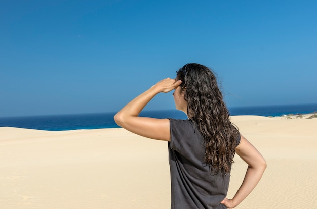Vue arrière de la femme brune avec sa main dans son front à la recherche de la mer.