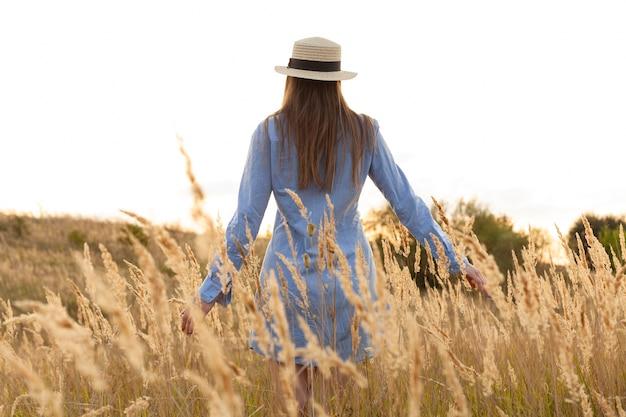 Vue arrière de la femme avec chapeau posant à travers les champs