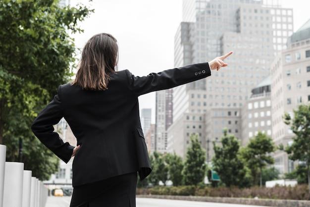 Vue arrière femme en costume pointant vers le haut