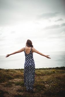 Vue arrière, femme debout, à, bras étendus