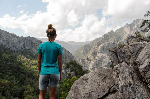 Vue arrière femme debout sur le rocher sur le magnifique paysage
