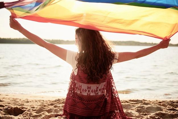 Vue arrière de la femme avec un drapeau arc-en-ciel sur la plage