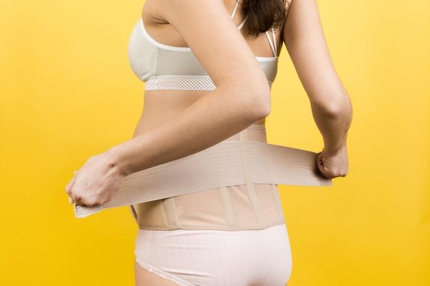 Vue arrière d'une femme enceinte en sous-vêtements mettant un bandage de soutien pour réduire les maux de dos sur fond jaune avec espace de copie. image recadrée du concept de ceinture de soutien abdominale orthopédique.