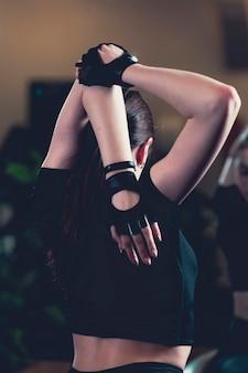 Vue arrière d'une femme exerçant dans la salle de gym