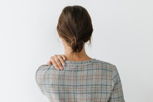 Vue arrière d'une femme fatiguée dans une robe à carreaux grise