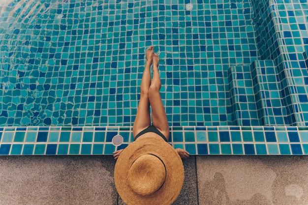 Vue arrière d'une femme gracieuse en maillot de bain et chapeau assis près de la piscine