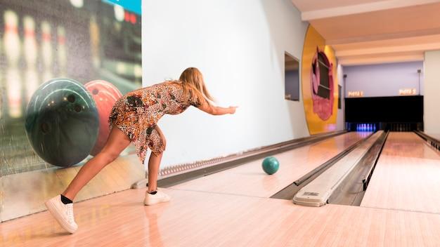 Vue arrière femme jouant au bowling