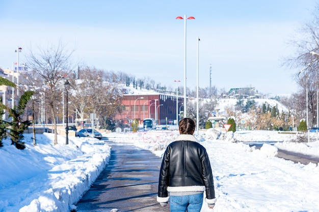 Vue arrière d'une femme marchant sur une avenue de la ville enneigée.