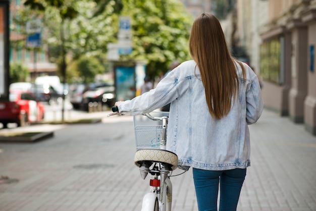 Vue arrière femme marchant à côté du vélo
