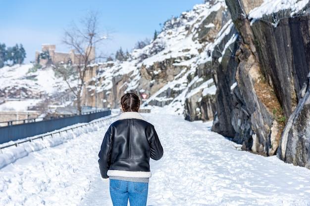 Vue arrière d'une femme marchant sur une route de ville enneigée.