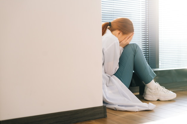 Vue arrière d'une femme médecin triste et déprimée pleurant assise près de la fenêtre tenant la tête et les bras sur le genou