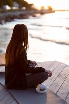 Vue arrière femme méditant à l'extérieur