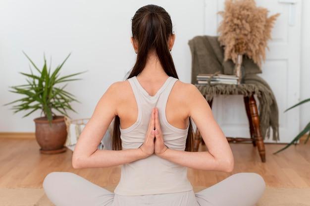 Vue arrière femme méditant à la maison