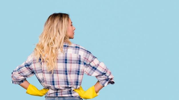 Vue arrière de la femme de ménage debout devant un fond bleu à la recherche de suite