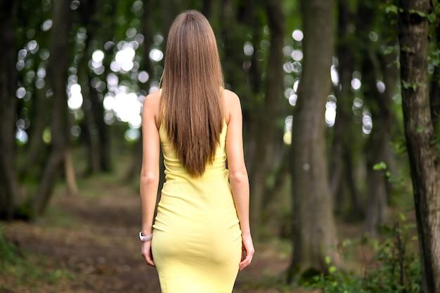 Vue arrière d'une femme mince en robe jaune debout dans une forêt sombre et sombre.