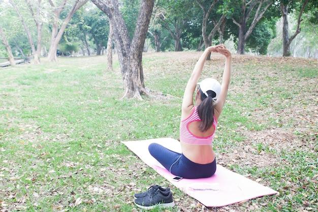 Vue arrière de la femme mince en vêtements de conditionnement physique exerçant dans le parc, beauté et santé con