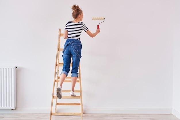 Vue arrière de la femme avec un mur de peinture au rouleau à peinture