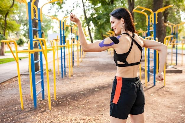 Vue arrière de la femme musclée brune souriante posant dans le parc et terrain de sport avec bande élastique sur l'entraînement du corps à l'extérieur