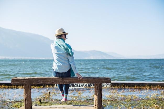 Vue arrière de la femme paisible assis sur un banc en bois